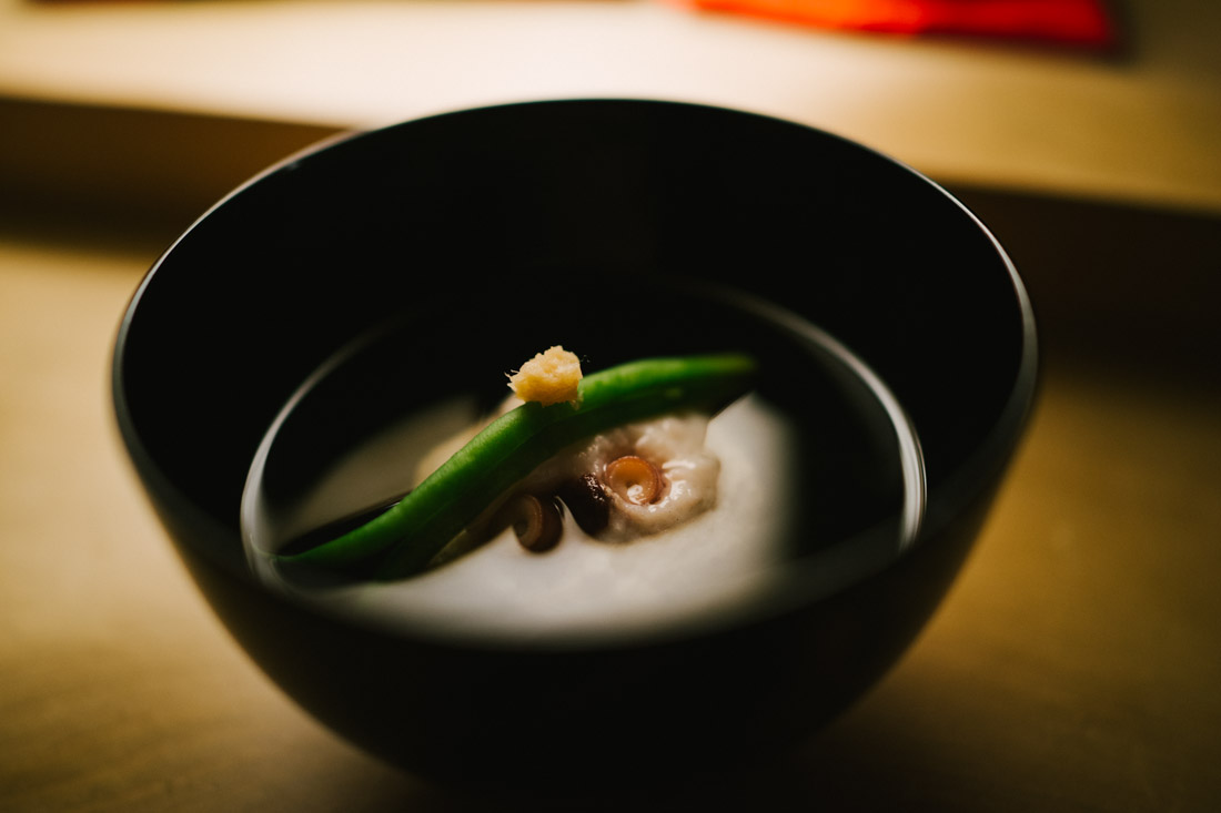 Clear soup with octopus dumpling and green bean, topped with ginger.